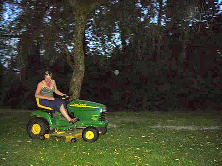 Bridget riding a lawn tractor at dawn.